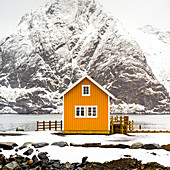 'A bright yellow building on the water's edge with a snow covered mountain in behind; Nordland, Norway'