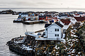 'Houses along the coastline with clouds over the ocean and horizon in the distance; Lofoten Islands, Nordland, Norway'