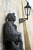 'Statue of a man leaning against a wall beside a light; Prague, Czech Republic'