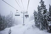 'Downhill skiiers ride the chairlift at a ski resort in the blowing snow and cloud; Whistler, British Columbia, Canada'