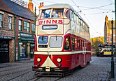 'Tram traveling along High Street in Beamish, the Living Museum of the North. These trams became fondly known as 'Balloons' because of their streamlined bloated appearance; Beamish, County Durham, England'