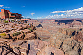 'The beautiful viewpoint at the West Grand Canyon Skywalk attraction, a group of tourists enjoys the skywalk while other tourists take photos on the edge of the canyon cliffs; Arizona, United States of America'