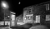 'A phone booth illuminated by a street lamp at nighttime outside a shop; Bamburgh, Northumberland, England'