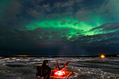 A man warms himself beside a driftwood fire while watching the aurora through clouds on the frozen Delta River, near Delta Junction, Alaska