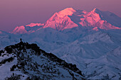 'A hiker on a ridge in Denali National Park is dwarfed by Denali at sunrise in winter; Alaska, United States of America'