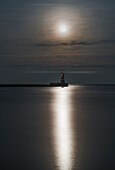 Roker Lighthouse at the end of a pier under a bright full moon reflecting on tranquil water, Sunderland, Tyne and Wear, England