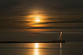 Roker lighthouse casts a light with the golden sunlight shining through cloud and reflecting on tranquil water, Sunderland, Tyne and Wear, England