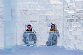 A young tourist couple poses inside of an ice castle build on the ice at Lake Louise in Banff National Park, Lake Louise, Alberta, Canada