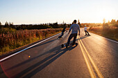 Three young men skateboarding down a road at sunset, Homer, Alaska, United States of America