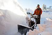 A young woman uses a snowblower in the deep snow, Homer, Alaska, United States of America