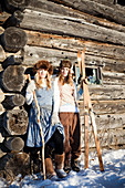 Portrait of two girls standing by a log cabin wearing fur hats holding skis and a walking stick, Homer, Alaska, United States of America