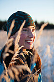 Portrait of a young woman wearing a knit hat and viewed through the tall grasses, Homer, Alaska, United States of America