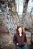 Portrait of a woman with red hair leaning on a tree and laughing with eyes closed, Homer, Alaska, United States of America