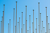 A accumulation of flagpoles in front of blue sky, Lisbon, Portugal