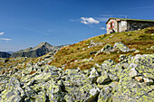 Person sitting in front of hut Mindener Huette, hut Mindener Huette, Tauern ridgeway, High Tauern range, Salzburg, Austria