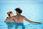 Couple relaxing together in pool, rear view
