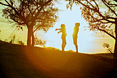 Couple enjoying nature, silhouetted by sun