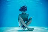 Boy resting in lotus position underwater