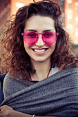 Woman wearing pink sunglasses, smiling cheerfully, portrait