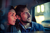 Couple looking out car window at night
