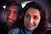 Couple looking out car window at night, portrait