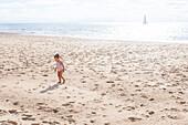 Kleines Mädchen zu Fuß am Strand