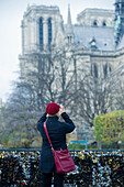 Tourist photographing Notre Dame Cathedral from Pont des Arts, Paris, France