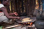 A woman roasts coffee beans on an open fire, Ethiopia, Africa