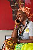 A woman smiling whilst talking on her mobile phone, Nigeria, West Africa, Africa