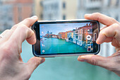 Europe, Italy, Veneto, Venice, Tourist taking a picture with smartphone on the Grand Canal in Venice