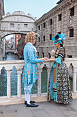 Europe, Italy, Veneto, Venice, Couple in carnival fancy dress near the Bridge of Sighs (Ponte dei Sospiri)