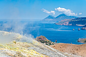 Volcano, Messina district, Sicily, Italy, Europe, Sulfur fumaroles on the crater rim of Vulcano, In the background the islands of Lipari and Salina