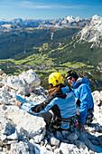 Climbers on rocks of the Ferrata Marino Bianchi admire the green valley of Cortina D'Ampezzo Dolomites Belluno Veneto Italy Europe