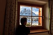 Ein Mann bewundert Sass De Putia umgeben von Schnee aus dem Glas eines Fensters Passo Delle Erbe Funes Tal Südtirol Italien Europa