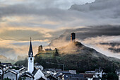 Misty sky on the alpine village of Ardez at sunrise, canton of Graubünden, district of Inn, lower Engadine, Switzerland, Europe