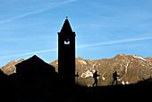Silhouettes of hikers at the old church at dawn, San Romerio Alp, Brusio, Canton of Graubünden, Poschiavo valley, Switzerland