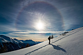 Skier climbing uphill under a 22° sun halo in winter, Muntuischè, Engadin, Switzerland