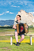 Alpe di Siusi/Seiser Alm, Dolomites, South Tyrol, Italy, Young woman playing with the accordion at the Alpe di Siusi