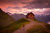 A hiker is almost at the Cabane du Mont Fort, a mountain hut near Verbier. The sunset puts the sky in pink and purple colors. It rained all day, and cleared just before this picture. The hut is one of the places hikers stay at during the Haute Route, a cl
