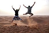 People jump in the Chegaga dunes in the Sahara desert in Morocco.