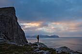 Female hiker stands below Møntind, Flakstadøy, Lofoten Islands, Norway