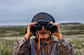A 4 year old Japanese American boy dressed as an explorer with a hat and vest surveys the land (grasslands and prairies) with his binoculars in Badlands National Park, South Dakota.