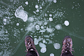 Man standing on translucent cracked ice wearing hiking shoes, only feet are visible.