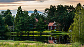 typical Swedish house reflecting in the waters of a lake close to Mora in Sweden in Summertime with trees all around and beautiful sky with clouds and nice sunset light.