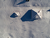 aerial view of a snowy landscape showing roofs of mountain refuges with skiers around on a sunny day in Vaud Canton, Jura mountains, Switzerland