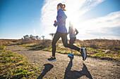 Frauen Trail laufen zusammen auf einem Küstenweg in Newport, Rhode Island, während des Frühlings