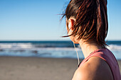 Woman in her twenties with earbuds working out during an early morning on the beach in Newport, Rhode Island