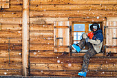Callum Pettit sits in the window of a log cabin in full ski gear while it snows. Verbier, Switzerland