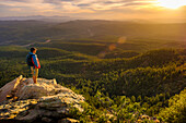 Tranquil scene with backpacker watching sunset from cliff, Mogollon Rim, Arizona, USA