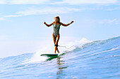 Front view of surfer girl on big wave Changgu, Bali, Indonesia